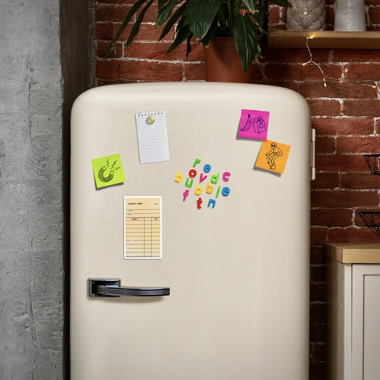 Retro fridge with assorted magnets including one with vintage library card artwork
